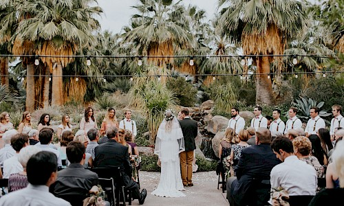Walk down the aisle surrounded by loved ones and the lush grove of trees.